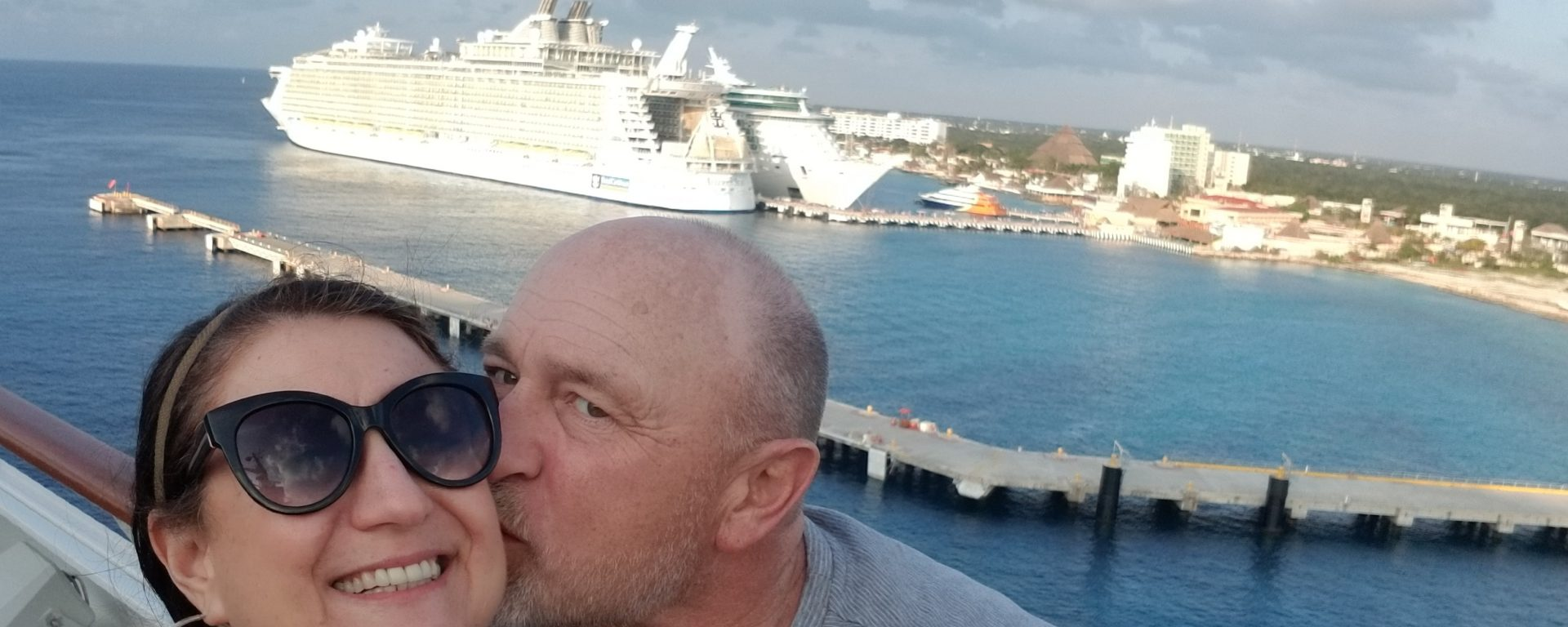 man kissing woman with cruise ship behind