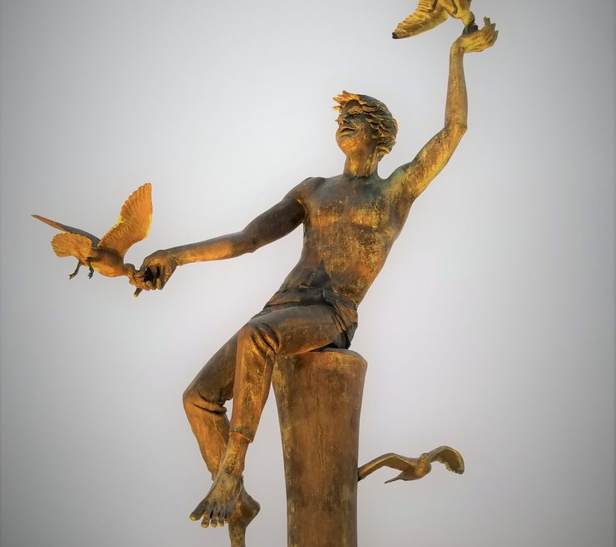 statute of man feeding the sea gulls next to the water with fog background