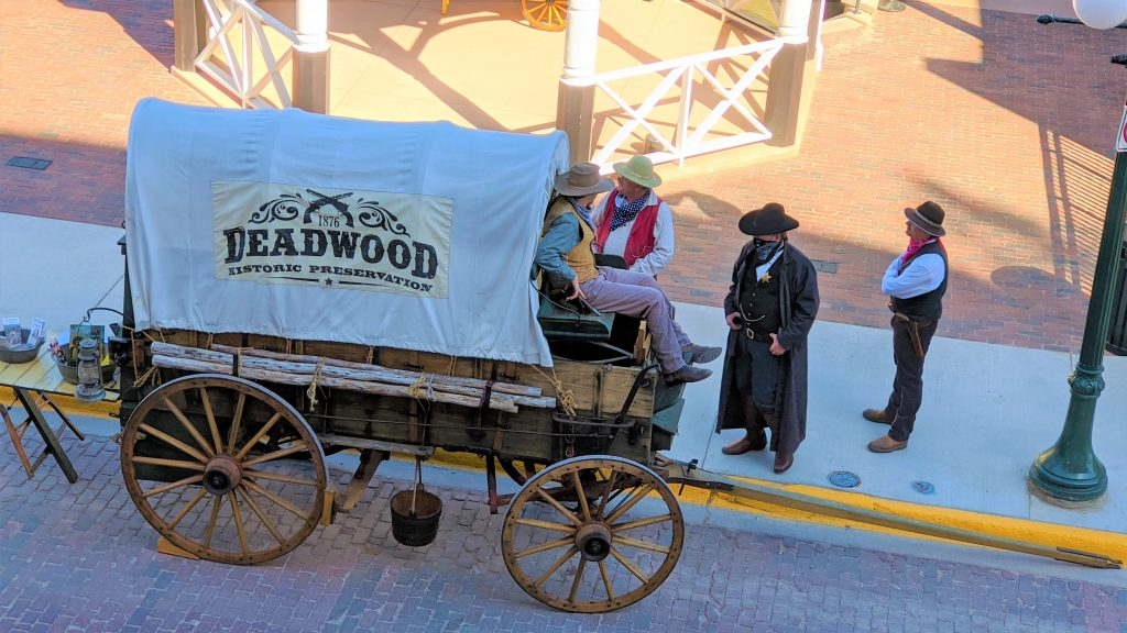 reenactors dressed in cowboy wear standing next to a covered wagon.