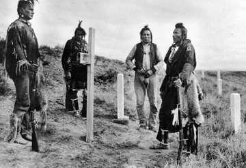 four Native Americans standing around headstones and crosses at the Little Bighorn battlefield