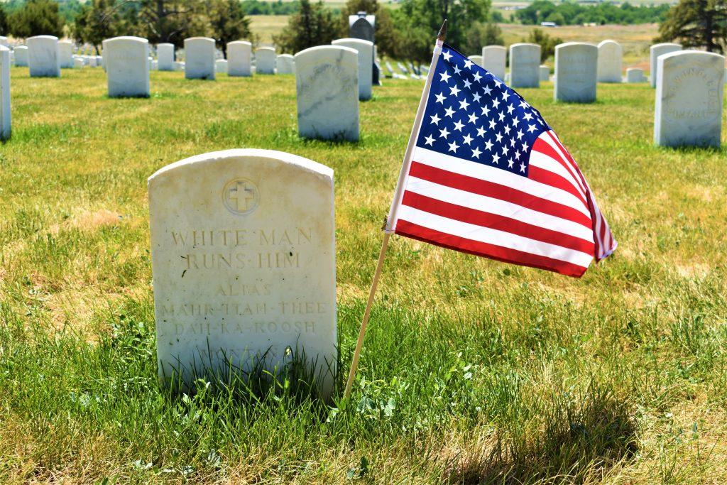 """Headstone in grass with United State flag. Reads """"White Man Runs Him Alias Mahr-Itah-Thee-Dah-Ka-Roosh."""" Other solider headstones in background. Cross on headstone"""