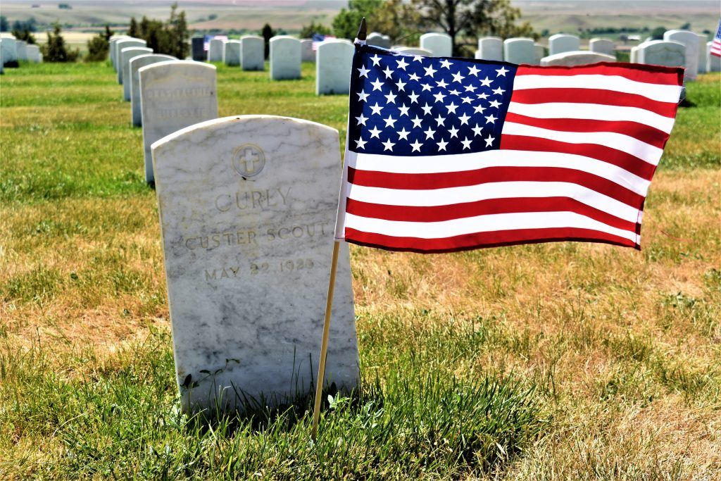"""headstone with United States flag. Reads """"Curly Custer Scout May 22, 1923"""""""