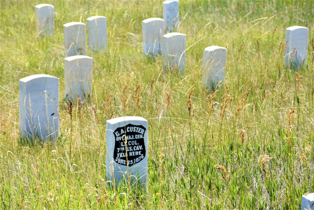 """headstones. One with black backing that reads """"G.A. Custer bvt. maj gen. Lt. Col. 7th U.S. CAV Fell Here June 25, 1876"""""""