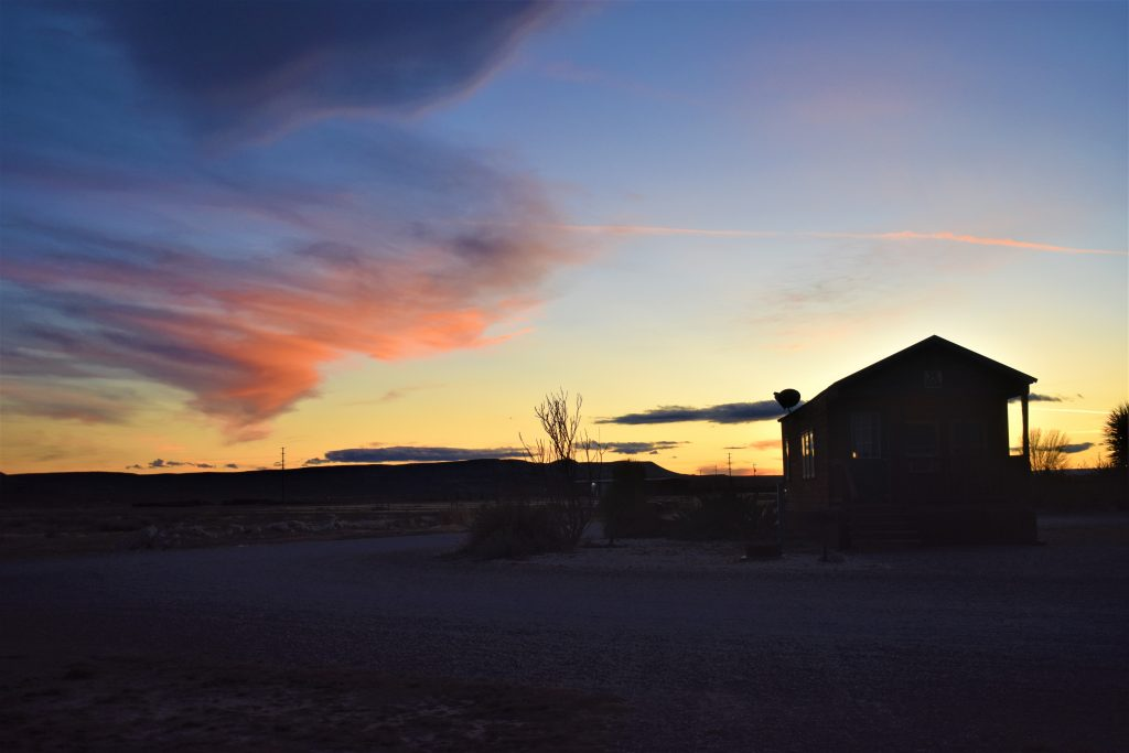 Sunset view of sky. Cabin is in silhouette.