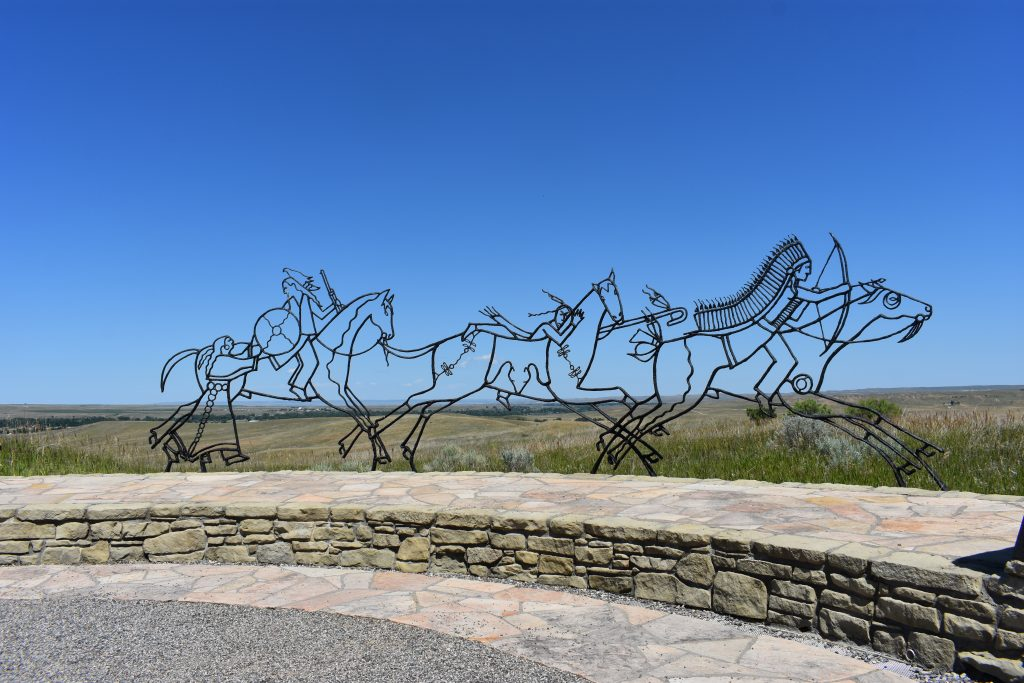 metal sculpture of native Americans fighting in the battle on horseback. Three warriors and one woman handing a shield to a warrior.