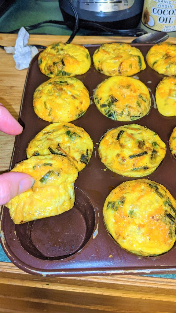 Hand pulling up one of Colorado Martini's Egg Bites from a muffin pan full of other egg bites.