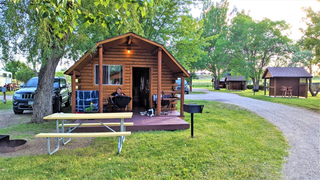 Man sitting at KOA cabin. Picnic bench and BBQ grill is in front of cabin. Other cabins to the right.