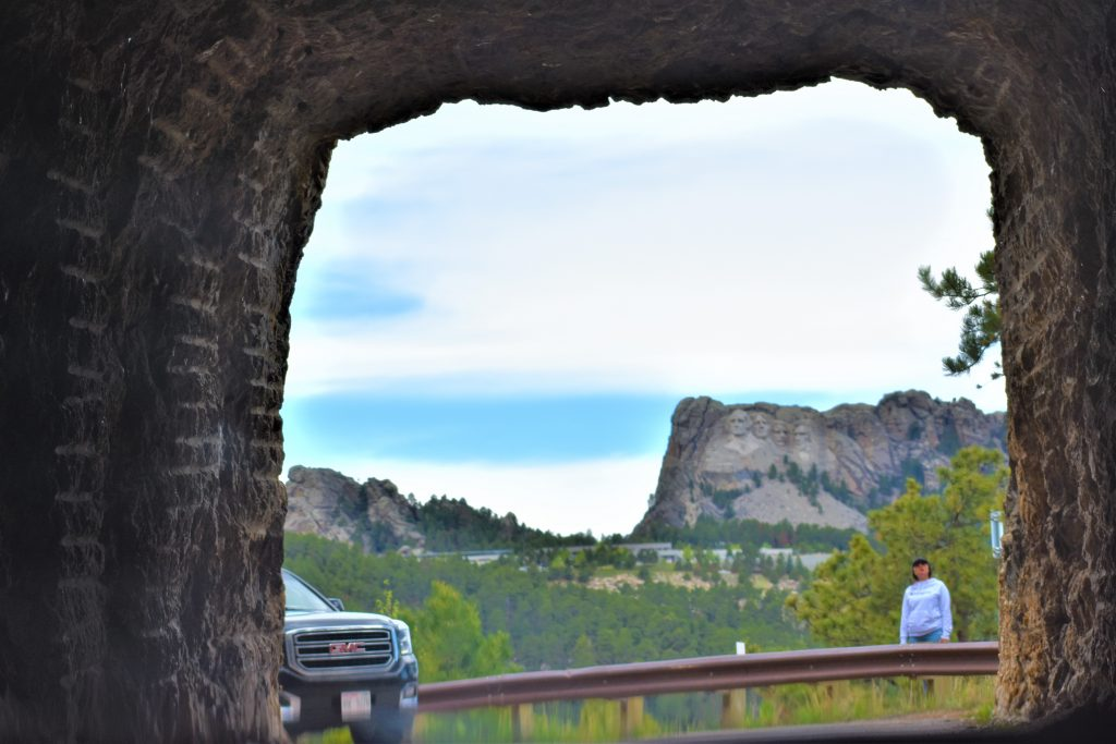 Iron Mountain Road tunnel in the Black Hills of South Dakota. Mount Rushmore in the distance. View of mount Rushmore from inside tunnel. Mount Rushmore is off in the distance. With green treed landscape between tunnel and Mount Rushmore. All presidents can be seen.