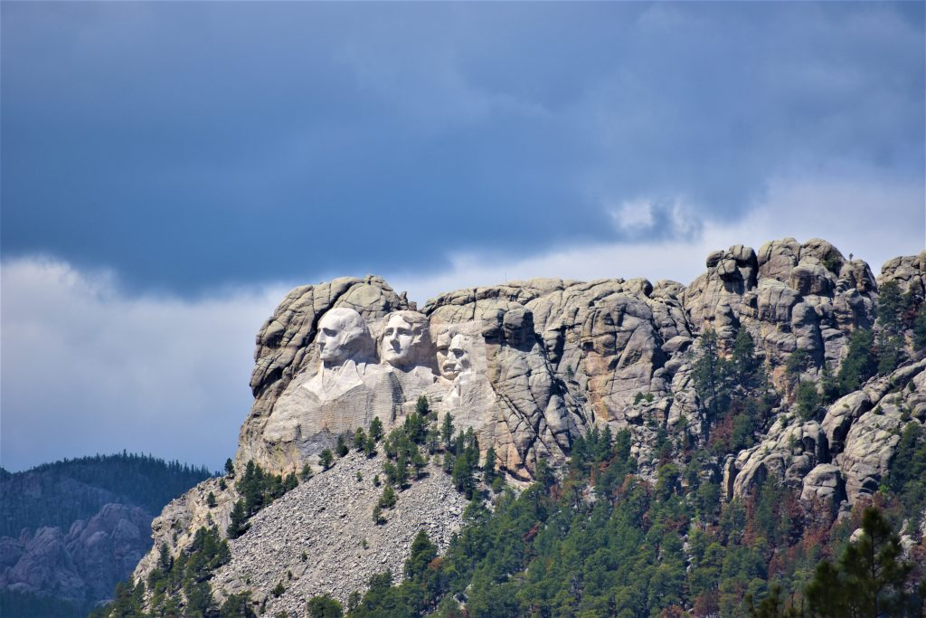 View of Mount Rushmore from cemetery. The heads of Washington, Jefferson, and side profile of Lincoln can be seen. Roosevelt is partially blocked. Storm cloud hovering above the rock face. Pine trees below the carving. Hills with pines in the background