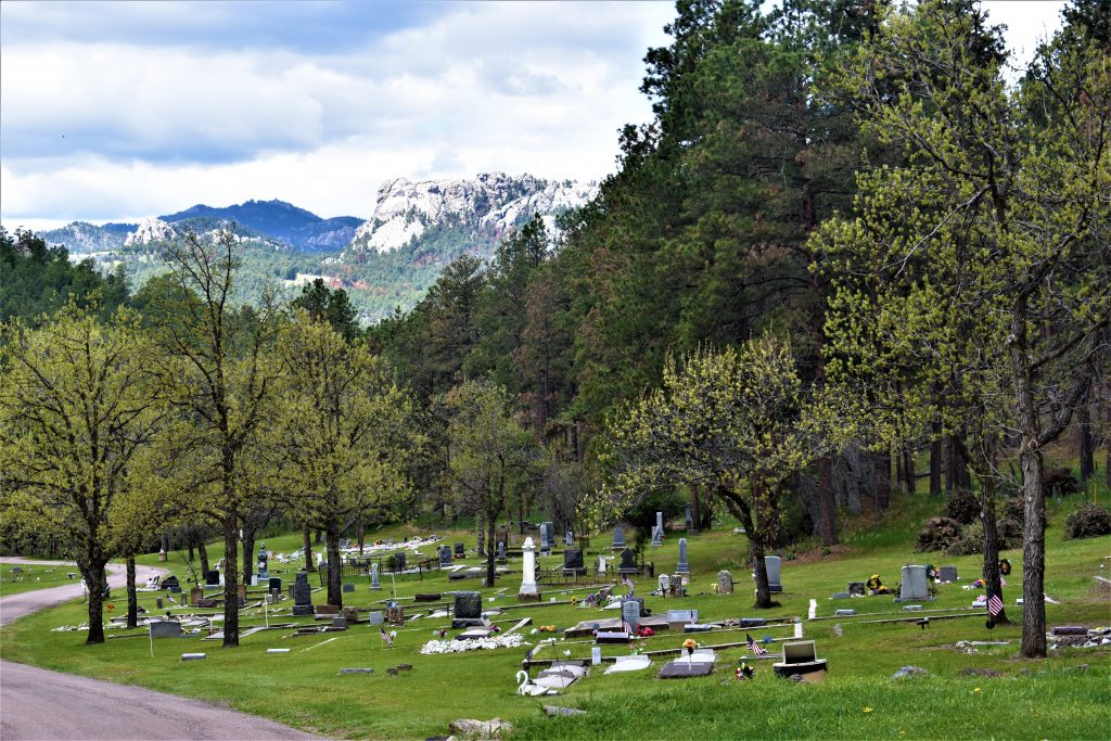 Keystone, South Dakota cemetery. Many headstones in the foreground. Mount Rushmore surrounded by pine covered pines in the background. Pine trees all around.