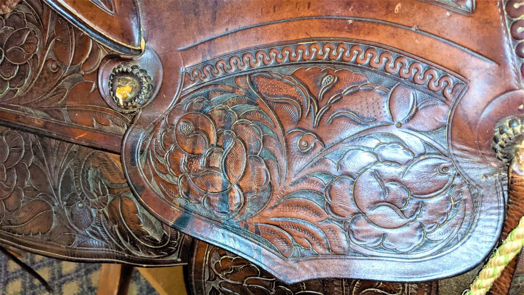 Sheridan flower style of leather carving. A close up of a saddle with the Sheridan flower style on the leather of the saddle.