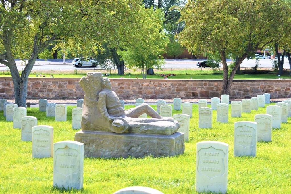 Santa Fe National Cemetery. Headstones. Focused on a personal headstone with a man sitting against a tree. Holding a hat. Wearing bullets in his belt. Western theme
