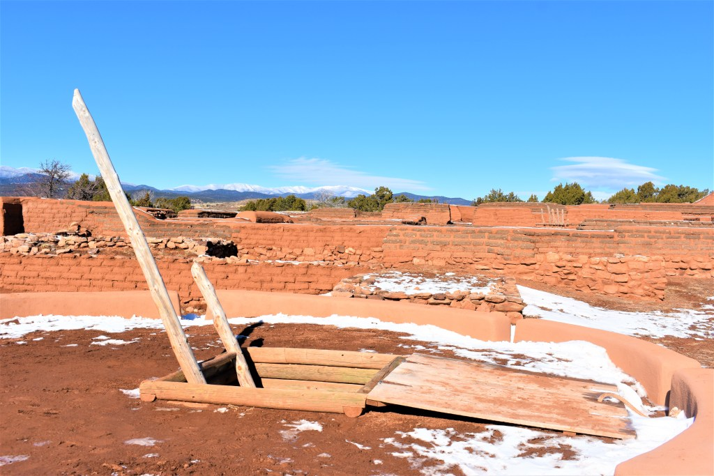 Trap door with a ladder. Reddish in color. It is called a Kiva. It was used in Pecos Native American Rituals