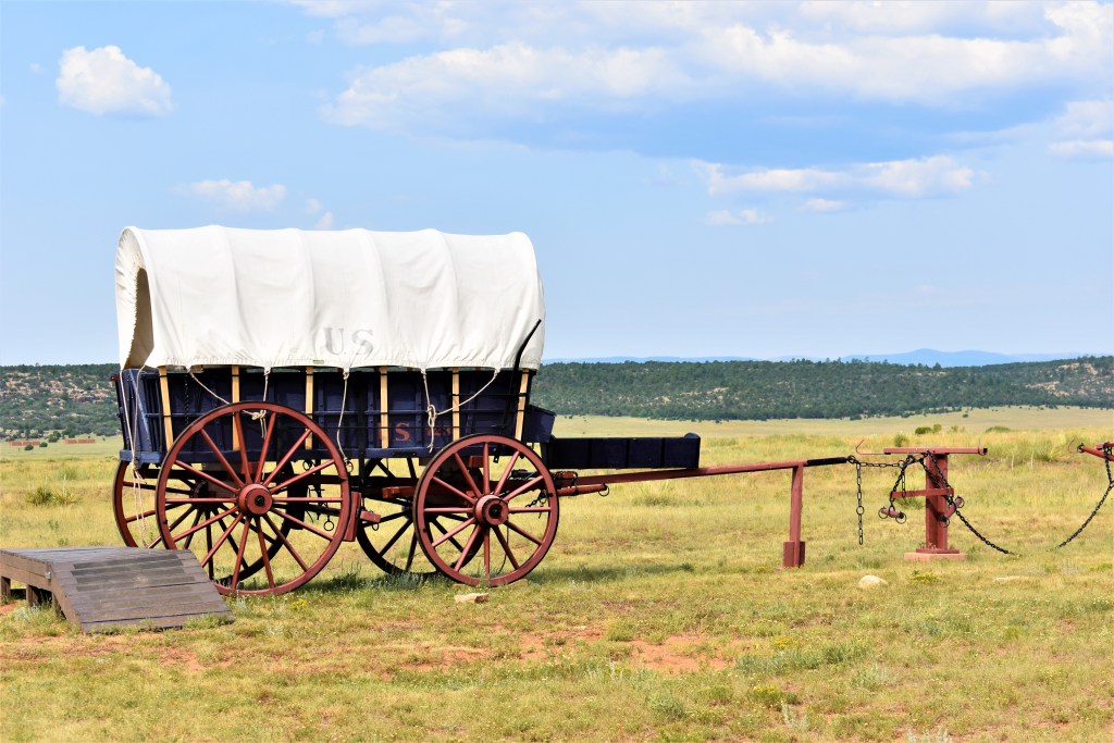 Covered wagon with U.S. on the sides at Fort Union Historical Park. Wagon is blue with red wheels.