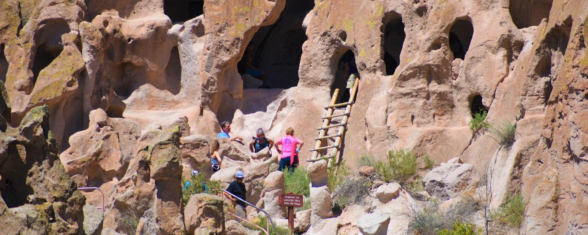 Rock face at Bandelier National Park. People climbing up a ladder to one of the Native American cave dewellings