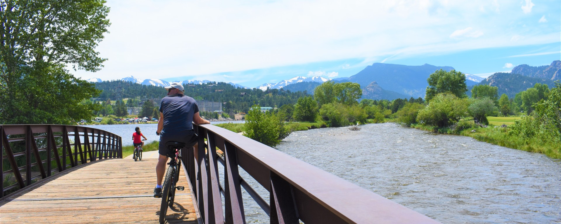 man at river on bridge and bike. Looking at mountains in Rocky Mountain National Park in Estes Park Colorado
