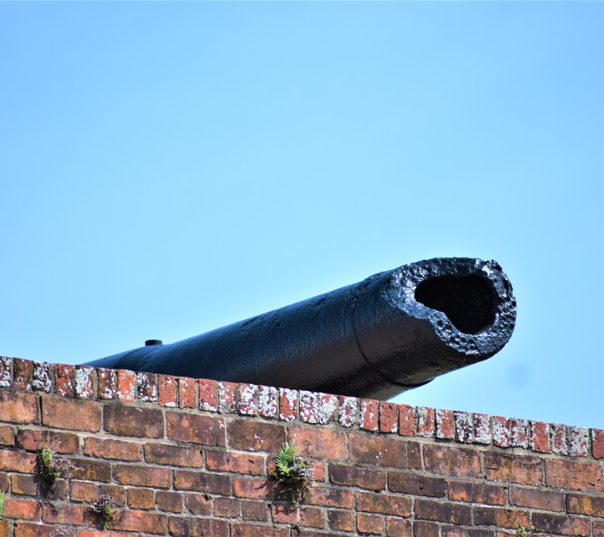 Black cannon which is broken at the tip. Sits on a red brick wall