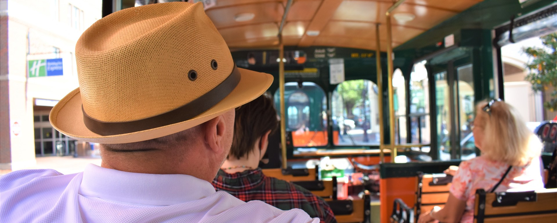 Man (Mr Martini) sitting on a Savannah trolley tour. It is his back side. He is wearing a panama hat.