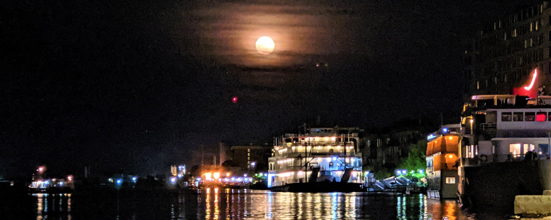 Supermoon over Savannah River with river boat in the foreground.